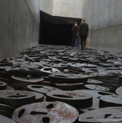 People walk on an exhibit in the Jewish Museum in Berlin, Germany on Saturday, Feb. 11, 2017. The visitors are walking on 10,000 steel faces which symbolize innocent lives lost in war.