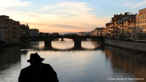 A man sits on the edge of the Ponte Vecchio (Old Bridge) during sunset on Saturday, March 11, 2017.