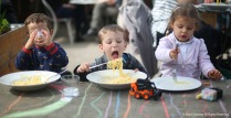 Ettore (left), Edoardo (center) and Camilla, all 2, enjoy lunch at a cafe ont he banks of the Arno River in Florence, Italy on Saturday, April 1, 2017.