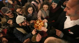 Florentines reach for free pizza during an event in Mercato Centrale (the main market) in Florence, Italy on Thursday, Jan. 27, 2017.