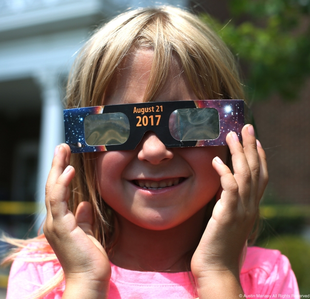 Alyssa, 6, of Ravenna poses for a portrait with her eclipse glasses on the front lawn of the Reed Memorial Library in Ravenna, Ohio on Monday, Aug. 21, 2017.