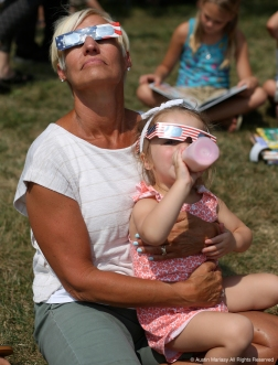 Lori Marchand, 61, and Riley Schlegelmilch, 2, watch the solar eclipse outside the Reed Memorial Library in Ravenna, Ohio on Monday, Aug. 21, 2017.