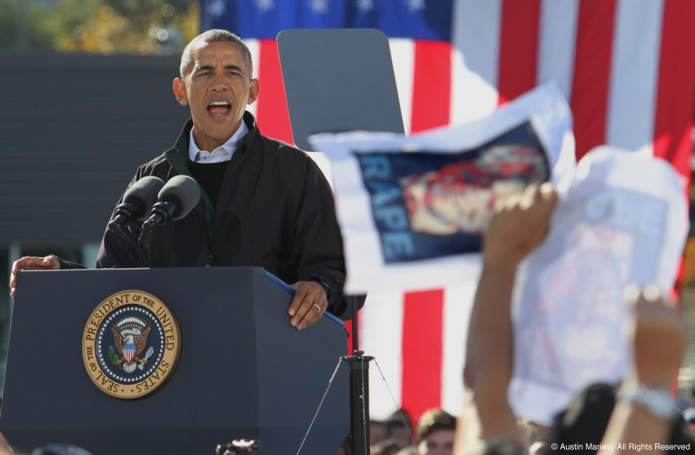 Then President, Barack Obama, responds to a protester during a campaign stop for then Democratic presidential nominee Hillary Clinton at Cleveland Burke Lakefront Airport in Cleveland, Ohio on Friday, Oct. 14, 2016.