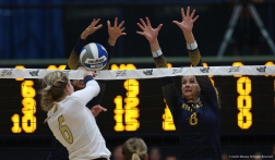 Kent opposite Heather Younkin (left) and middle blocker Annie Ennesser block a spike during a match against the University of Akron on Friday, Sept. 22, 2017.