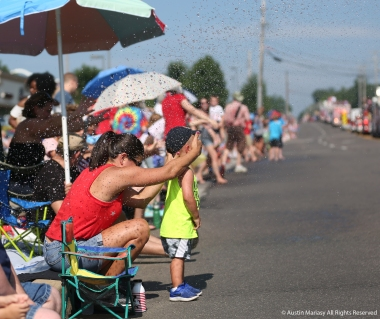 Kristin Lenton shields Beckett's eyes from water sprayed by Valley Fire District at the Stow fourth of July Parade.