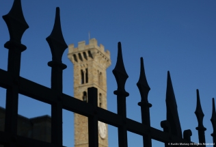 The steeple of the Fiesole Cathedral can be seen through a fence in Fiesole, Italy.
