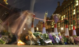 A Londoner places flowers on a makeshift memorial outside the Parliment building in London, England after British-born Khalid Masood, 52, ran his car though a crowd of people before ramming the perimiter fence around the Parliament building and stabbing a police officer to death.