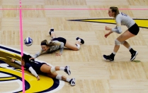 Kent State defensive specialists Challen Geraghty (bottom), and Claire Tulisiak dive for the aballl while outside hitter Kelsey Bittinger watches during a match against Buffalo University on Thursday, Oct. 27, 2017.
