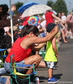 Kristin Lenton shields her son Beckett's eyes as the Valley Fire District rides by and sprays water on spectators of the Stow, Ohio fourth of July Parade. Temperatures reached 92 degrees in Stow but it felt much hotter on the parade route.