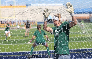 Eastern Michigan goal keeper Chelsea Abbotts lifts up the net during warmups before a game at Kent State University on Sunday, Sept. 24, 2017.