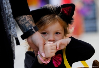 London, 2, hides behind her mom's hand during trick or treating in downtown Kent on Friday, Oct. 27, 2017.