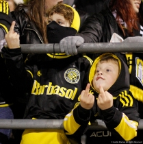 """Donavan, 10 (left), and Alex, 7, flip off owner of the Columbus Crew Sc during the first leg of the playoff match against Toronto FC on Tuesday, Nov. 21, 2017. Columbus fans are angry over the owner's threats to move the team to Austin, Texas if he cannot get a stadium in downtown Columbus. Chants of """"Fuck you Precourt we are the Crew"""" echoed through Mapfre Stadium throughout the match."""