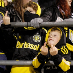 "Donavan, 10 (left), and Alex, 7, flip off owner of the Columbus Crew Sc during the first leg of the playoff match against Toronto FC on Tuesday, Nov. 21, 2017. Columbus fans are angry over the owner's threats to move the team to Austin, Texas if he cannot get a stadium in downtown Columbus. Chants of ""Fuck you Precourt we are the Crew"" echoed through Mapfre Stadium throughout the match."