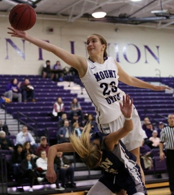 Mount Union freshman forward Sarah Hessel jumps over the back of John Carroll junior guard Kahrin Spear in an attempt to recover a rebound on Wednesday, Jan. 24, 2018.