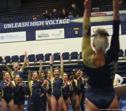 Senior Rachel Stypinski celebrates with her team after she finished her performance on the balance beam on Friday, Jan. 19, 2018.