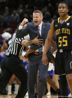 University at Buffalo head coach Nate Oats is held back by a referee after running on the court to celebrate a play with his team during the Mid-American Conference semifinal game in Cleveland, Ohio