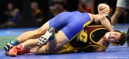 Central Michigan's Jordan Atienza struggles as California State University, Bakersfield's Matt Williams attempts to pin him during their bout at the NCAA Wrestling Championship in Cleveland.