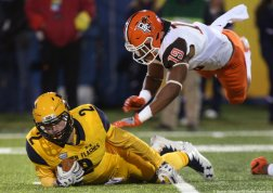 Bowling Green State University's Brandon Harris dives over Kent State's George Bollas during their game at Dix Stadium in Kent, Ohio.