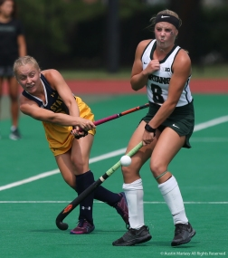 Kent State junior forward Laila Richter hits the ball while Michigan State junior forward Maggie Cole reacts.
