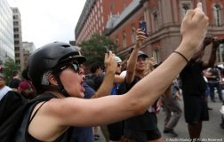 A woman flips off a group of about 30 white supremacists as they enter Lafayette Park, in front of the White House, as part of the Unite the Right Rally in Washington D.C. on Saturday, Aug. 12, 2018.
