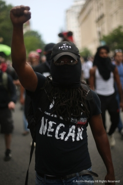 A demonstrator with the Antifa black block raises a fist while on patrol outside the Unite the Right Rally 2.