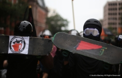 Antifa protesters try to hide their faces behind skateboards as they march through the streets of Washington D.C. after the Unite the Right Rally 2