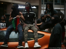 Demonstrators walking with Antifa sit on top of a car after the Unite the Right Rally 2 in Washington D.C.