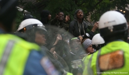 Protesters flip off police at the start of the clash between Antifa and police officers. Police came up behind the Antifa march with the intention of keeping the group moving but the group turned on police and that lead to the depolyment of pepper spray.