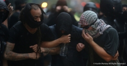 Antifa Black Block protesters link arms and react to pepper spray during a clash with metro police on G Street after the Unite the Right Rally 2.