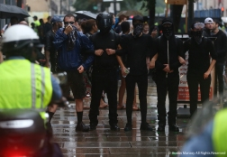 Antifa Black Block protesters link arms and standoff with police during a clash in which pepper spray was fired at the protesters.