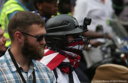 White supremacists dressed in protective padding and helmets with Go Pros that cover the face walk down the street under heavy police protection at the beginning of the Unite the Right Rally 2.