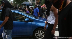The Antifa Black Block protesters surround a car after they blocked an intersection in Washington D.C. after the Unite the Right Rally 2.