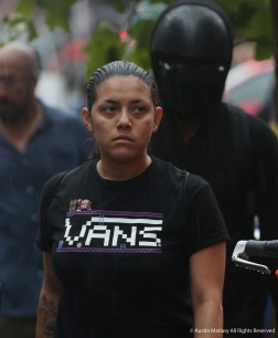 """A D.C. native scowls as Antifa marches through the streets knocking over trash cans and newspaper stands. She yelled """"not in my fucking city"""" as the marchers were starting to become destructive."""