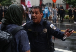 Officer Robert Morris of the Washington D.C Metropolitan Police Department keeps protesters and media on the sidewalk as police clash with Antifa Black Block rioters after the Unite the Right Rally 2.