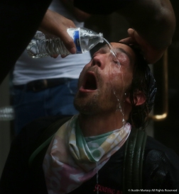 An Antifa Black Block protester has his eyes flushed after being hit with pepper spray during a clash with police.