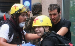 """An Antifa Black Block medic tends to someone who took a face full of pepper spray while another medic (front) yells at media to """"get the fuck out of here,"""" during a clash with police after the Unite the Right Rally 2 in Washington D.C."""