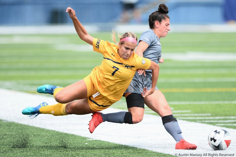 Kent State's junior defender Yasmine Hall falls while bat4tling with St. Bonaventure's freshman midfielder Emily Foltz.