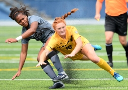 Kent State's sophomore midfielder Maddie Holmes falls while battling for the ball with St. Bonaventure's junior midfielder Sabrina Sousa-Sampson during a match at Kent State University.