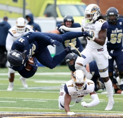 The University of Akron's senior tight end Newman Williams flips over Kent State's junior corner back Jamal Parker during a the rivalry game on Saturday, Oct. 20, 2018.