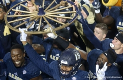 The University of Akron football team holds the Wagon Wheel trophy after defeating its rivals, Kent State, for the fourth year in a row.
