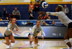 Kent State's senior defensive specialist Kaeleigh Stang (18) and junior outside hitter Ashley Makruski (16) both dive to provide back up to junior middle backer Myla King as she fields the ball against Northern Illinois University.