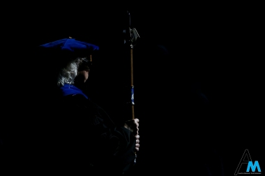 The standard bearer stands at attention holding the official Kent State University Mace at the opening of the Fall 2018 master's commencement ceremony on Friday, Dec. 14, 2018.