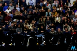 Graduates sit and wait for the Kent State University graduate student commencement to begin.