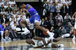 Florida Gulf Coast's redshirt sophomore forward Troy Baxter Jr. jumps over Michigan State's junior guard Joshua Langford after he fell while trying to pick up a loose ball during the Spartans' home opener on Sunday, Nov. 11, 2018.