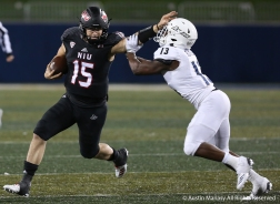 Northern Illinois Unviversity redshirt sophomore quarterback Marcus Childers stiff arms University of Akron's redshirt junior corner back Denzel Butler durign the game at the University of Akron on Nov. 1, 2018.