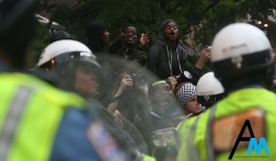 Protesters flip off police at the start of the clash between Antifa and police officers. Police came up behind the Antifa march with the intention of keeping the group moving but the group turned on police and that lead to the deployment of pepper spray.