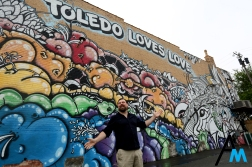 Matthew Taylor gestures to the wall he designed and painted with artist Mede on Adams Street in downtown Toledo. The mural was commissioned by Art Corner Toledo in an effort to help beautify downtown.