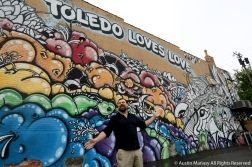 Matthew Taylor gestures to the wall he designed and painted with artist Mede on Adams Street in downtown Toledo.