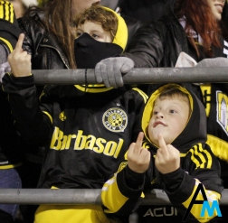 """Donavan, 10 (left), and Alex, 7, flip off owner of the Columbus Crew's former owner during the first leg of the playoff match against Toronto on Nov. 21, 2017. Columbus fans are angry over the owner's threats to move the team to Austin, Texas if he cannot get a stadium in downtown Columbus. Chants of """"C-R-E- double U Fuck you Precourt we are the Crew"""" echoed through Mapfre Stadium throughout the match."""