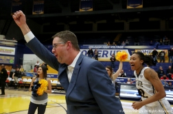 Kent State's head women's basketball coach, Todd Starkey runs through a tunnel towards the victory bell after he won his 200th game as a head coach.